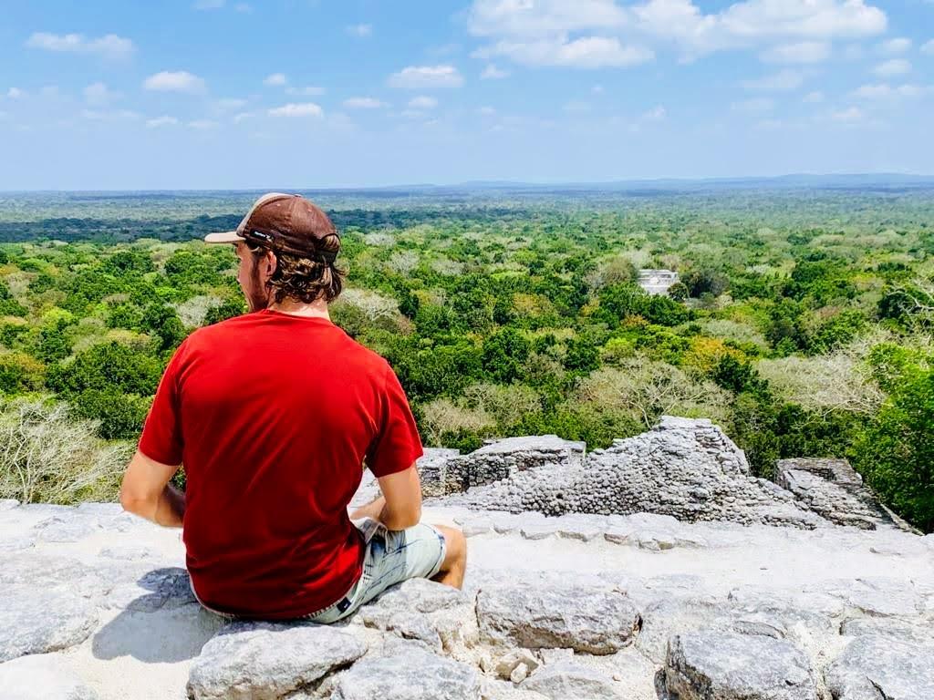 Damien à Calakmul assis sur un rocher avec la jungle et des ruines Mayas en arrière plan