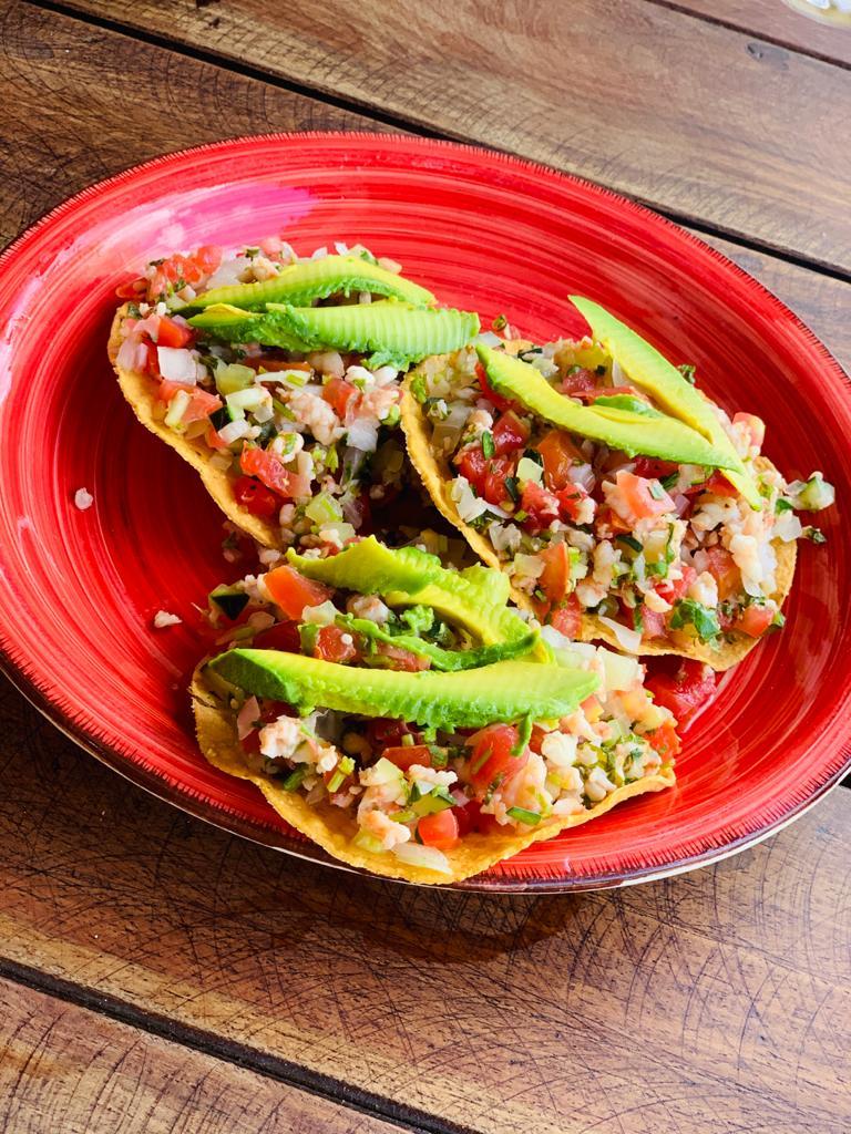 Trois tacos dans une assiette rouge sur une table en bois